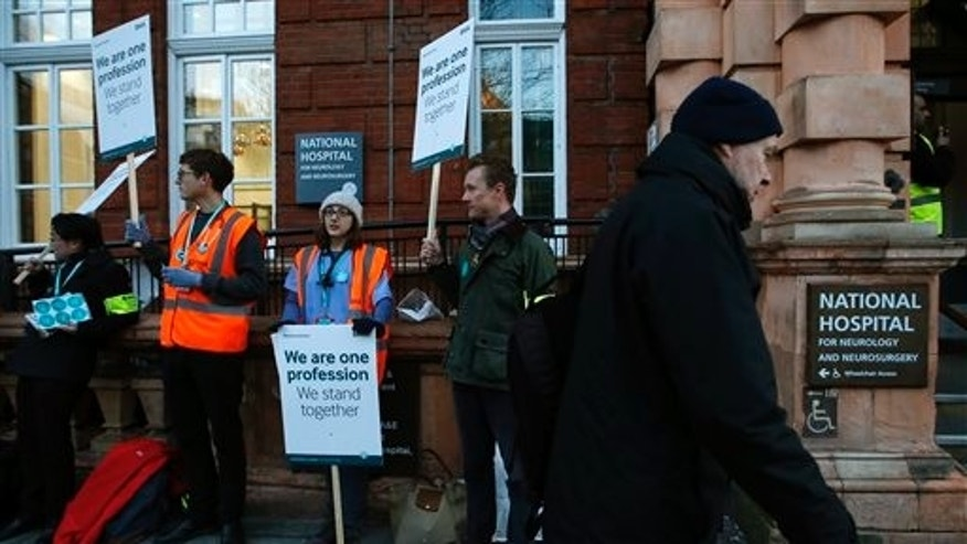 Keir Pickard, second left, a junior doctor at the National Hospital for Neurology and Neurosurgery, hands out stickers on the picket line in London,Tuesday, Jan. 12, 2016. Thousands of junior doctors have walked off the job in England in a dispute over pay and working conditions - the first such strike in 40 years. Some 50,000 junior doctors - who represent a third of the medical workforce - are on strike for 24 hours amid government plans to change pay and work schedules. (AP Photo/Alastair Grant)