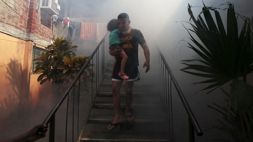A man walks away from his home with his son as health workers fumigates the Altos del Cerro neighbourhood as part of preventive measures against the Zika virus and other mosquito-borne diseases in Soyapango, El Salvador January 21, 2016. REUTERS/Jose Cabezas