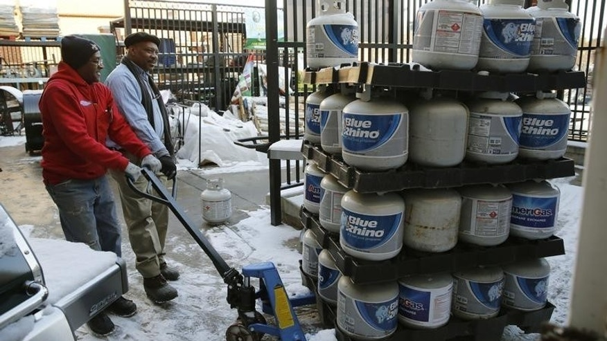 Employee Michael Torney (L) moves a pallet of propane gas tanks at Strosniders Hardware store in Silver Spring, Maryland January 21, 2016. REUTERS/Gary Cameron