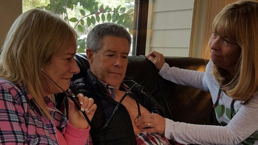 Linda Meyer, (l.), listens to her deceased son's heart beat inside transplant recipient Jim Keegan, as Keegan's wife Diane looks on.