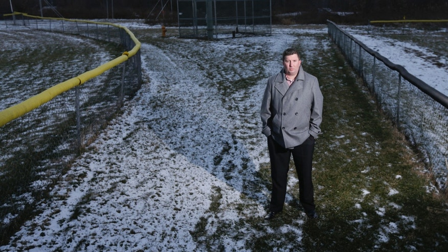 In this Thursday, Jan. 21, 2016 photo, Michael Hickey poses near Hoosick Falls municipal well 7 between two baseball fields in Hoosick Falls, N.Y. Federal regulators have warned residents of an upstate New York factory village near the Vermont border not to drink water from municipal wells, and a plastics plant has agreed to supply bottled water and pay for a new filtration system. The action this month resulted from a quest by Hickey to find out why so many people in Hoosick Falls had cancer. (AP Photo/Mike Groll)