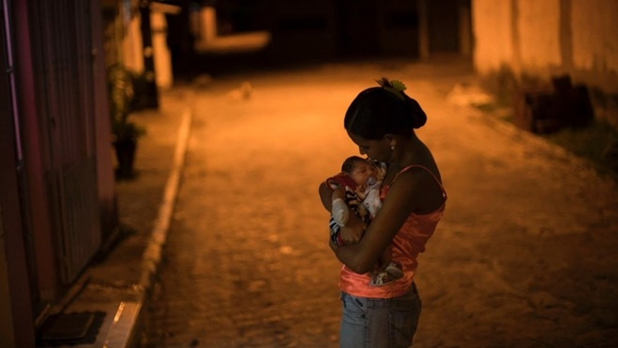 In this Jan. 26, 2016 photo, Daniele Ferreira dos Santos holds her son Juan Pedro, who was born with microcephaly, outside her house in Recife, Pernambuco state, Brazil. Santos was never diagnosed with Zika, but she blames the virus for her sons defect and for the terrible toll it has taken on her life. (AP Photo/Felipe Dana)