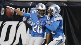Detroit Lions strong safety Don Carey (left) is congratulated by strong safety Isa Abdul-Quddus after his 40-yard fumble recovery for a touchdown during the first half.