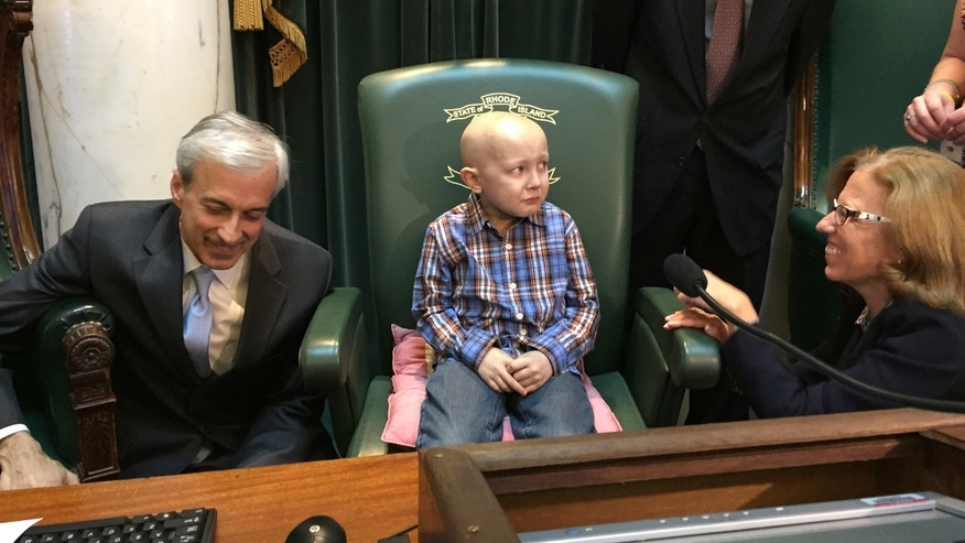 "Dorian Murray, 8, of Westerly, R.I., is a bit overwhelmed as he sits in the Statehouse Senate Chamber in Providence, R.I., Wednesday, Jan. 20, 2016 as he is honored by Rhode Island lawmakers, from left, Majority Leader Dennis Algiere, State Rep. Brian Kennedy and Senate President Teresa Paiva Weed, who proclaim it ""#DSTRONG Day"" in a general assembly resolution. Murray, who has a rare and untreatable form of pediatric cancer, has said his final wish was to become famous in China. (AP Photo/Matt O'Brien)"