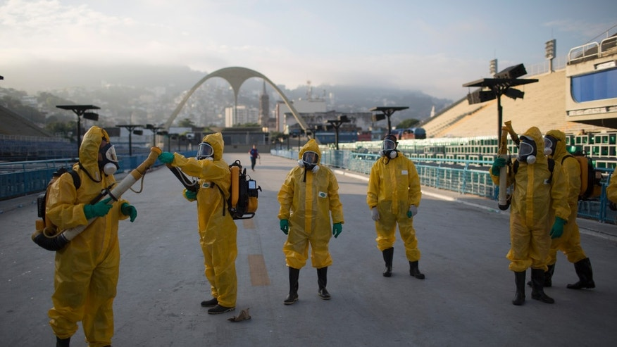 Health workers get ready to spray insecticide to combat the Aedes aegypti mosquitoes that transmits the Zika virus under the bleachers of the Sambadrome in Rio de Janeiro, Brazil, Tuesday, Jan. 26, 2016. Inspectors begin to spray insecticide around Sambadrome, the outdoor grounds where thousands of dancers and musicians will parade during the city's Feb. 5-10 Carnival celebrations. Brazil's health minister says the country will mobilize some 220,000 troops to battle the mosquito blamed for spreading a virus linked to birth defects. (AP Photo/Leo Correa)