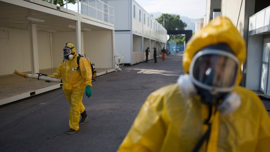 A health worker sprays insecticide to combat the Aedes aegypti mosquitoes that transmits the Zika virus at the Sambadrome in Rio de Janeiro, Brazil, Tuesday, Jan. 26, 2016. Inspectors begin to spray insecticide around Sambadrome, the outdoor grounds where thousands of dancers and musicians will parade during the city's Feb. 5-10 Carnival celebrations. Brazil's health minister says the country will mobilize some 220,000 troops to battle the mosquito blamed for spreading a virus linked to birth defects. (AP Photo/Leo Correa)