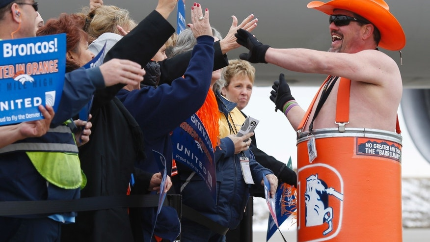 Todd McKernan, right, son of the late Denver Broncos Barrel Man Tim McKernan, rallies fans as they wait for the team's players to board an airplane at Denver International Airport on Sunday, Jan. 31, 2016. The Broncos will face the Carolina Panthers Sunday, Feb. 7, in Super Bowl 50. (AP Photo/David Zalubowski)
