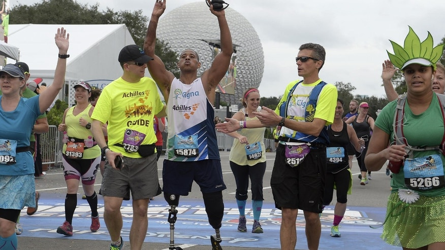 Master Sergeant Cedric King, who lost both legs during an IED explosion in 2012, completed the Walt Disney World Marathon with Cigna's CEO David Cordani (right).PHOTOGRAPH BY PHELAN M. EBENHACK