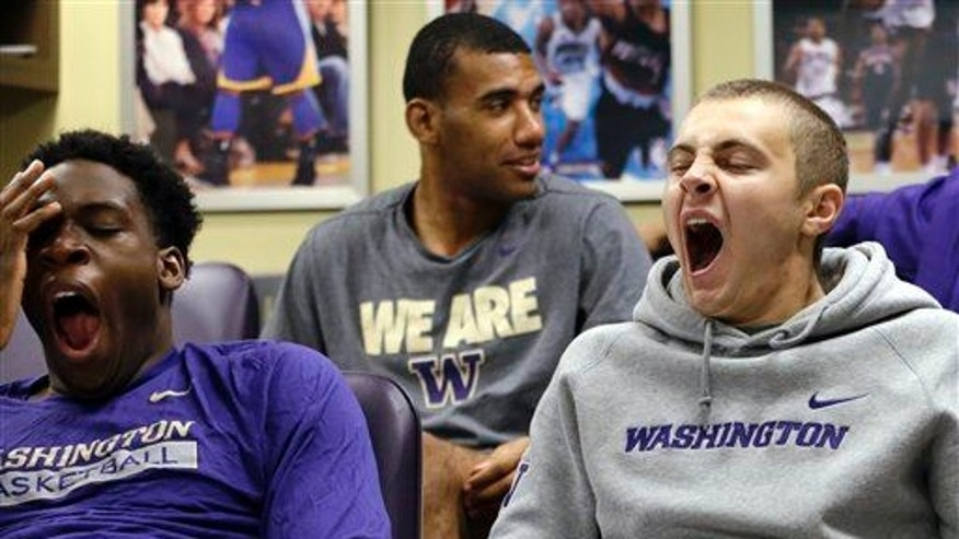 In this photo taken Sept. 28, 2015, Washington men's basketball players yawn as a classmate sits behind them during a class in Seattle.