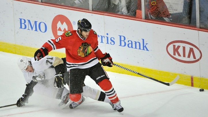 FILE - In this Sept. 30, 2011 file photo, Chicago Blackhawks defenseman Steve Montador, right, and Pittsburgh Penguins center Evgeni Malkin, of Russia, go for the puck during the first period of a preseason NHL hockey game, in Chicago. Montador is among a group of plaintiffs in a lawsuit brought against the NHL over concussion repercussions that has grown to well over 100 former players, who believe the league ignored a duty to warn them of the risks of head injuries.   (AP Photo/Brian Kersey, File)