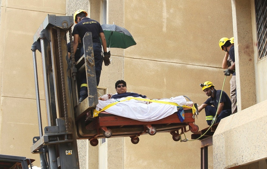 Saudi Civil Defence members use a forklift to move Khaled Mohsen Shaeri, 20, from his house in the Saudi city of Jizan, and to be airlifted to the capital Riyadh for medical treatment, August 19, 2013. Shaeri weighs approximately 610 kg (1345 lbs) and is suffering from severe obesity due to health problems that have resulted in a rapid increase in his weight over the past two years. REUTERS/Faisal Al Nasser (SAUDI ARABIA - Tags: HEALTH SOCIETY TRANSPORT TPX IMAGES OF THE DAY) - RTX12QVT