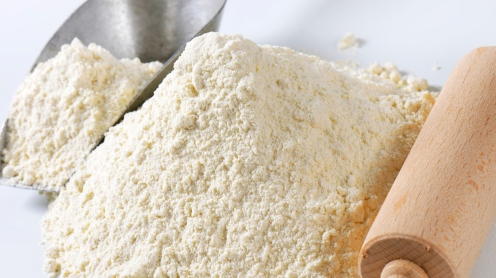 Pile of finely ground flour, wood rolling pin and metal scoop
