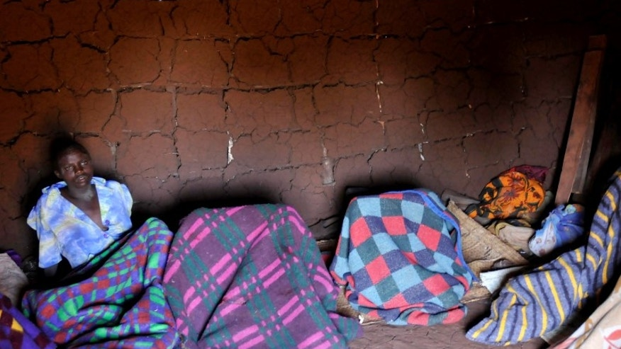 A teenager from Uganda's Sebei tribe sits inside a mud hut after undergoing female genital mutilation in Bukwa district