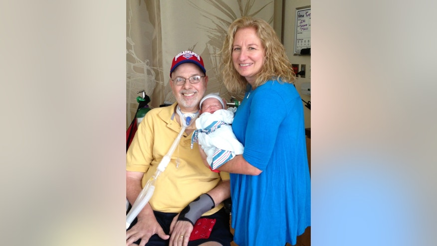 Joe and Donna Swider pose for a photo with their newest grandchild, Shea.