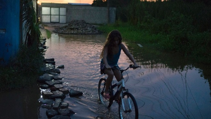 In this Jan. 29, 2016 photo, a girl rides her bike through a flooded street in the Parque Sao Bento shantytown of Rio de Janeiro, Brazil. Authorities are focusing on the most effective way to combat the Zika disease: killing the mosquito that carries the virus. Fumigation is one method; another is seeking out and draining standing water where the insect lays its eggs. Brazil is in the midst of a Zika outbreak and authorities say they have also detected a spike in cases of microcephaly in newborn children, but the link between Zika and microcephaly is as yet unproven. (AP Photo/Andre Penner)