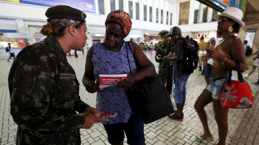 A Brazilian Army soldier distributes pamphlets with information to combat the Aedes aegypti mosquito during the National Day of Mobilization Zika Zero at Central train station in Rio de Janeiro