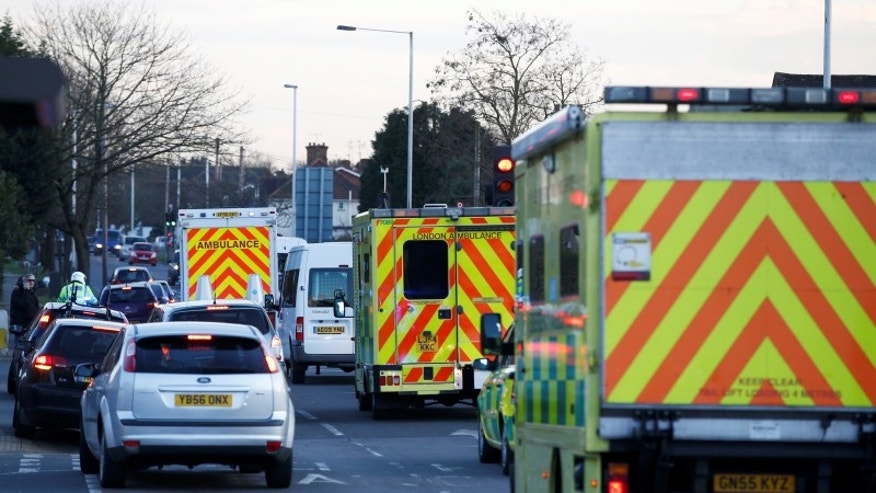 Nurse Pauline Cafferkey is driven an away by ambulance (L) in a convoy after landing at Northolt just west of London
