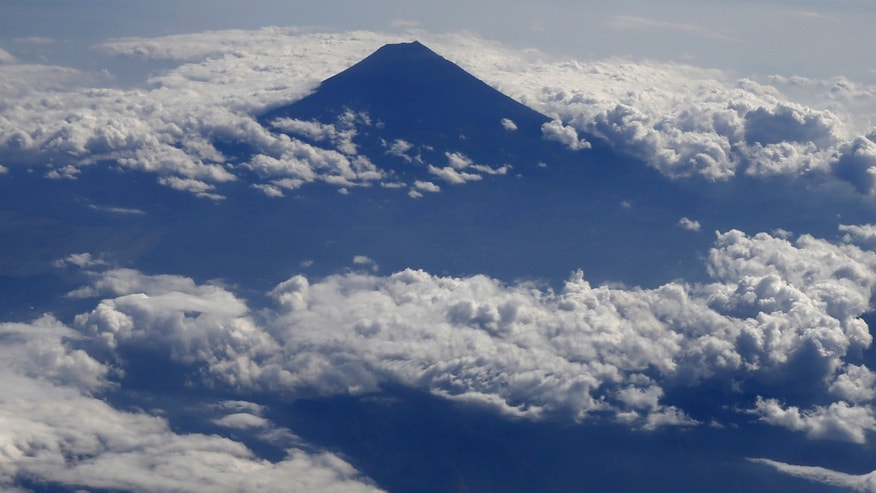Japan's Mount Fuji, surrounded by cloud, is seen from an airplane October 6, 2015. Mount Fuji, at 3,776 metres (12,388 ft) is Japan's highest mountain.  REUTERS/Toru Hanai - RTS3757