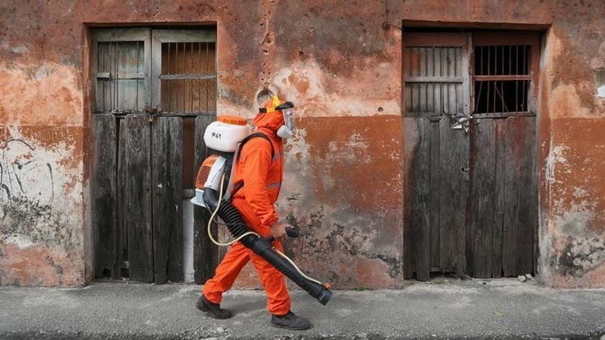 State health worker walks towards a house to fumigate it as part of preventive measures against the Zika virus and other mosquito-borne diseases in Merida