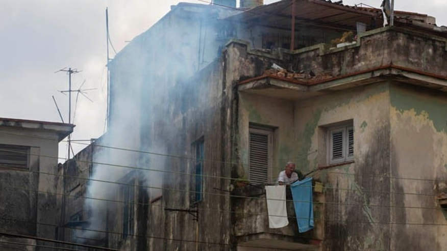 A man stands outside on his balcony as soldiers fumigate inside his home in Havana, Cuba, Feb. 22, 2016.