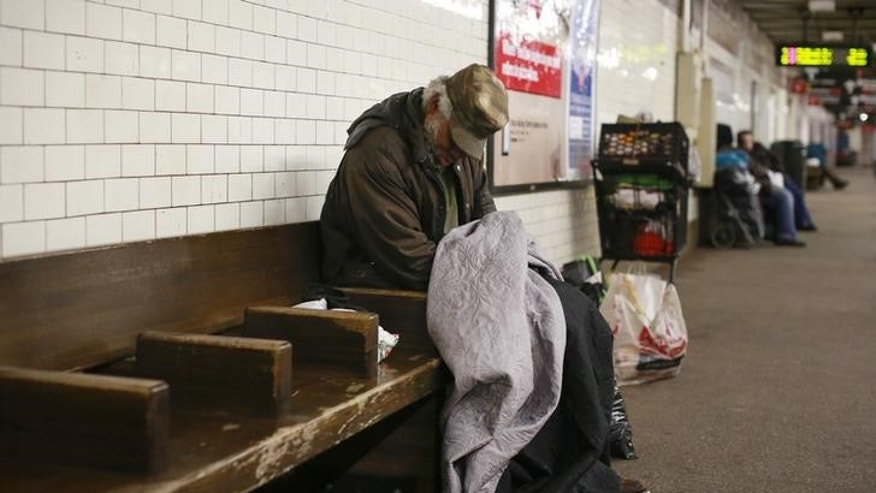 A man sleeps on a seat at the Borough Hall subway station in the Brooklyn borough of New York