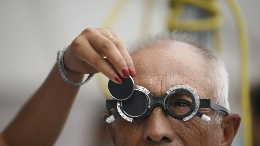 A man receives an eye exam as an ophthalmologist changes a lens during a health campaign in the suburb of Escobedo