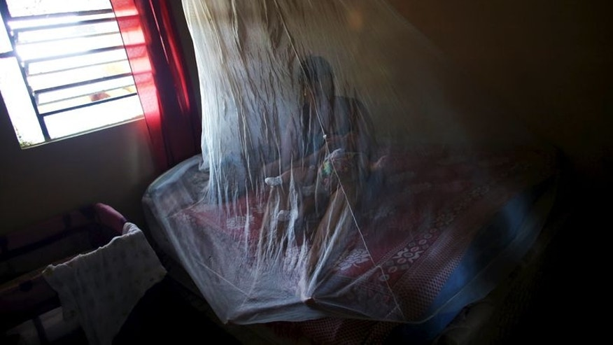 Vanessa, feeds her daughter Valentina, who is 5-months old and born with microcephaly, with a bottle under a mosquito net, inside their house in Jaboatao