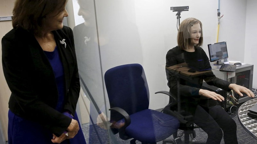 NTU Professor Thalmann looks at a humanoid as she is set up for an interview in Singapore