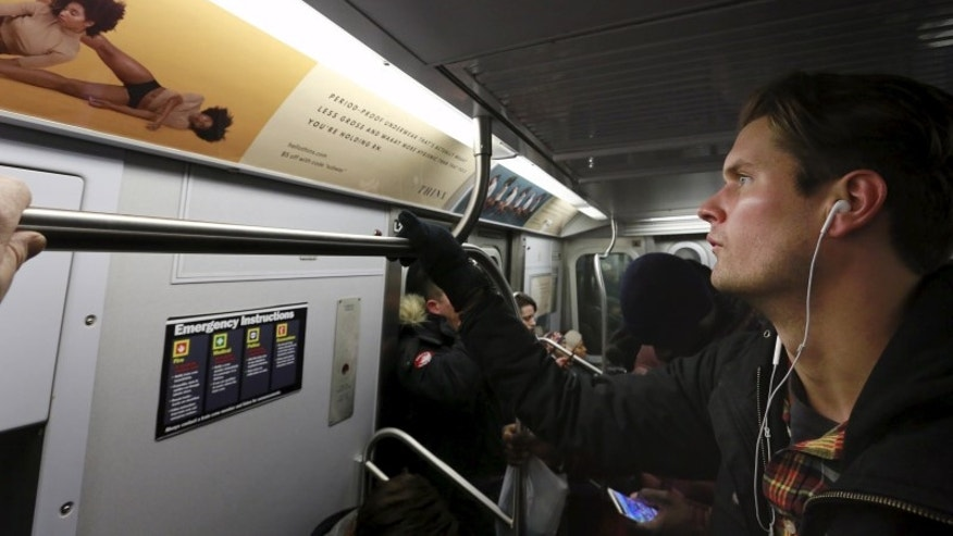 "A commuter looks at advertisements for Thinx brand ""period proof underwear"" as he rides the subway in New York"