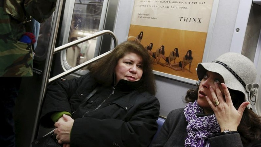 "Commuters sit underneath advertisements for Thinx brand ""period proof underwear"" as they ride the subway in New York"