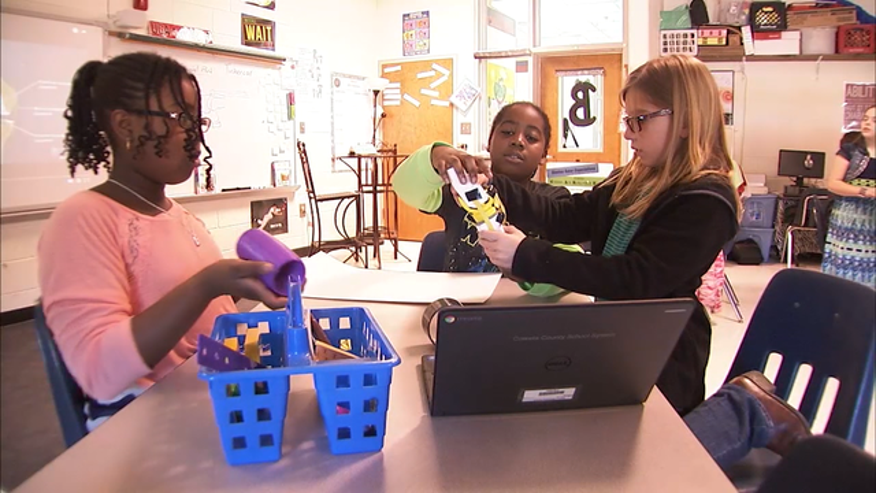 Students at Glanton Elementary School study the 3-D printed knee they designed