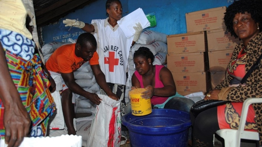 Red Cross workers distribute food at a World Food Programme storage center in Monrovia