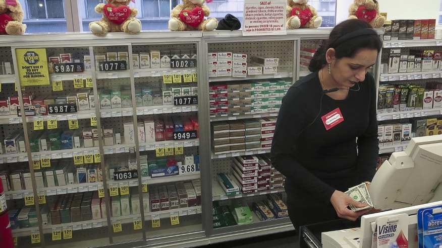 A cashier counts money in front of shelves full of cigarettes at a CVS store in the Manhattan borough of New York.