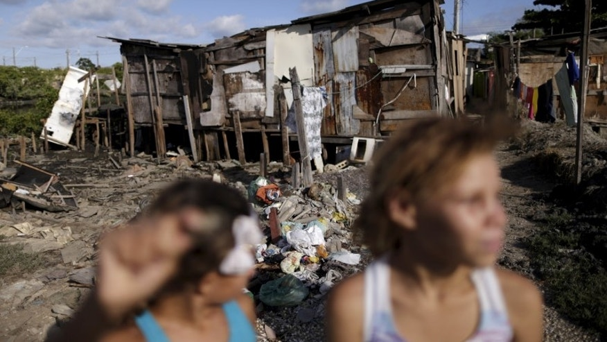 """Children are pictured near dwellings known as palafitte or """"Palafita"""" in Recife"""