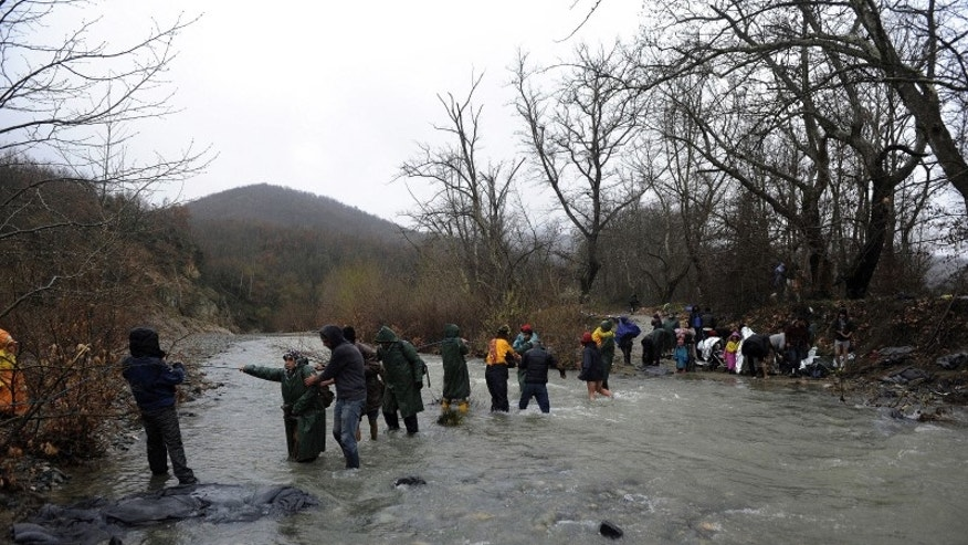 Refugees and migrants cross a river near the Greek-Macedonian border to return to Greece, after an unsuccessful attempt to enter Macedonia, west of the village of Idomeni, Greece
