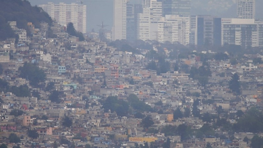 Buildings and houses stand shrouded in smog in Mexico City