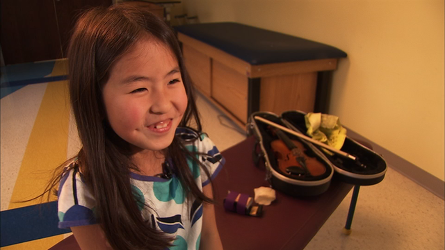 Danielle Fairchild uses an assistive device to help her hold her violin. She was born with a disabled dominant hand.