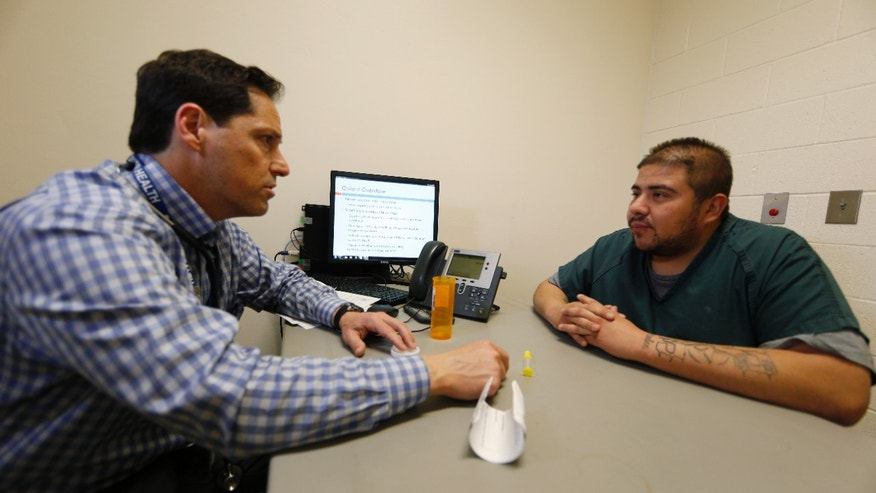In this Tuesday, March 1, 2016, photograph, Dr. Josh Blum, left, confers with inmate Lee Gonzales at the Denver County Jail in downtown Denver. Jails and correction agencies across the country such as Denver are teaching soon-to-be-released inmates how to use the heroin overdose antidote called naloxone, either to save others and sometimes themselves. (AP Photo/David Zalubowski)