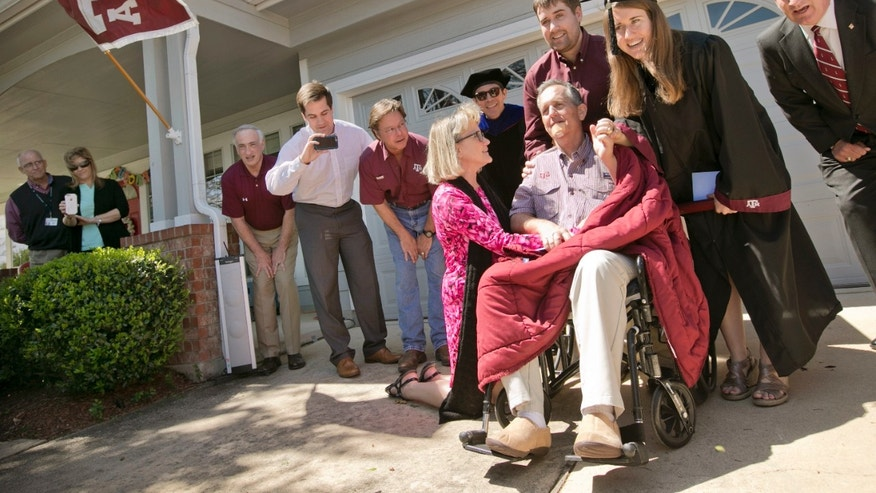"Jim Brewer, center, sings ""The Sprit of Aggieland"" during the graduation ceremony for his daughter Jenny Brewer, right, from Texas A&M at his home in Circle C Ranch Tuesday March 22, 2016 in Austin. Brewer, 57, is nearing the end of his struggle with pancreatic cancer, watched his daughter graduate from Texas A&M University,his alma mater. Doctors said Brewer's time is short, Texas A&M brought the ceremony to his home as dozens of relatives, neighbors and friends looked on, many wearing Aggie maroon."