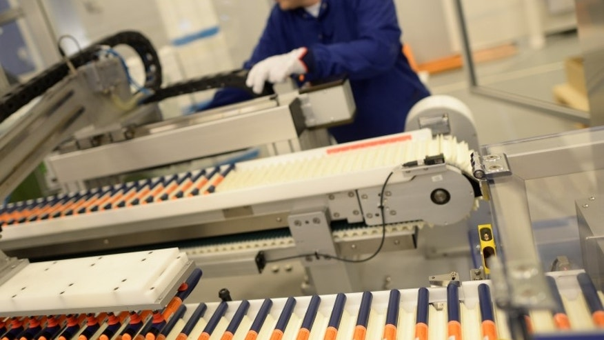 A Novo Nordisk employee controls a machine at an insulin production line in a plant in Kalundborg