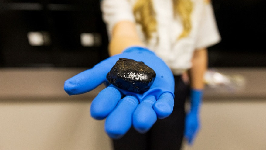 A police officer holds black tar heroin in Post Falls, Idaho.
