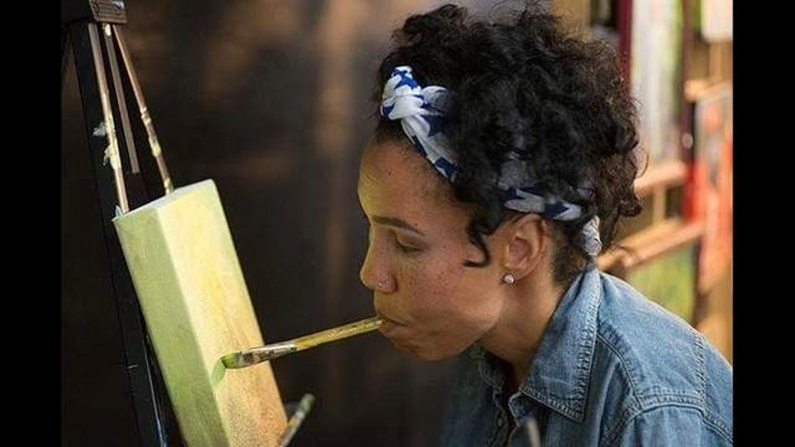 Alana Ciena Tillman, who is in her 30s, has a rare birth defect that has left her unable to move some of her joints, including those in her arms. She uses her feet and mouth to paint.