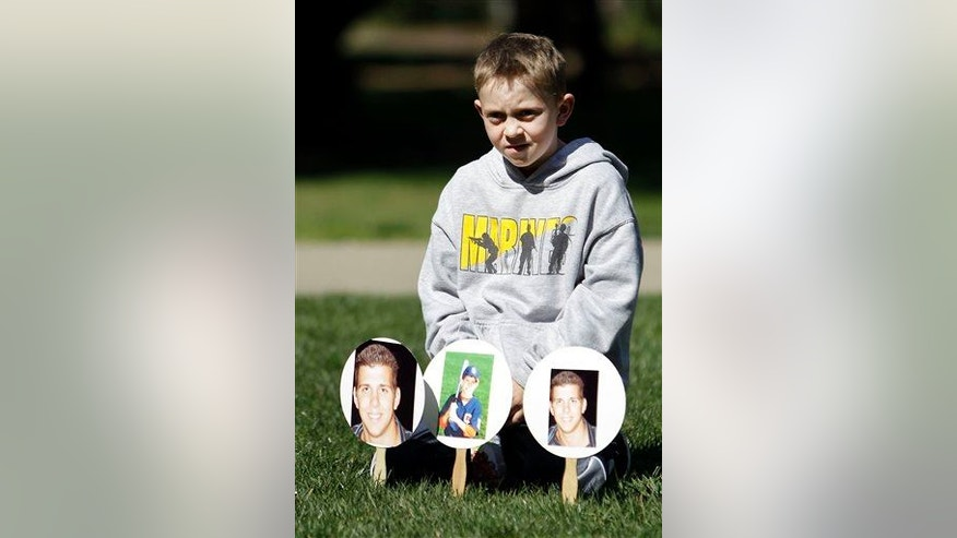Christopher Hansen sits with photos of his late uncle, Joey Rovero, who died in 2009 after mixing prescription drugs and alcohol. The demonstration was held in Sacramento on Monday, March 11, 2013.