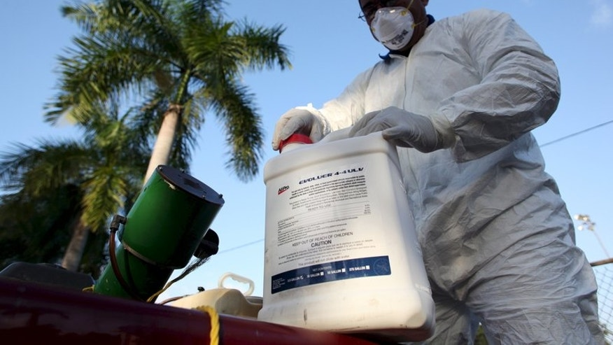 File photo of a health worker preparing insecticide before fumigating a neighborhood in San Juan