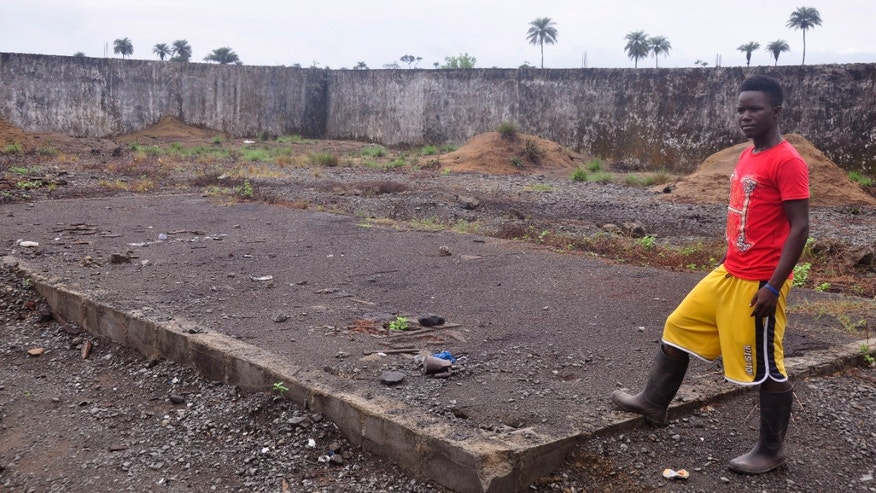 In this photo taken Saturday, March 26, 2015, a boy, stands next to a place that was used to stack bodys of Ebola victims at a crematorium in Boys Town on the outskirts of Monrovia, Liberia. As Liberia marks the second anniversary Wednesday of its first confirmed Ebola cases, many neighbors say they want to see the crematorium torn down so they can try to forget that terrible time. (AP Photo/ Abbas Dulleh)