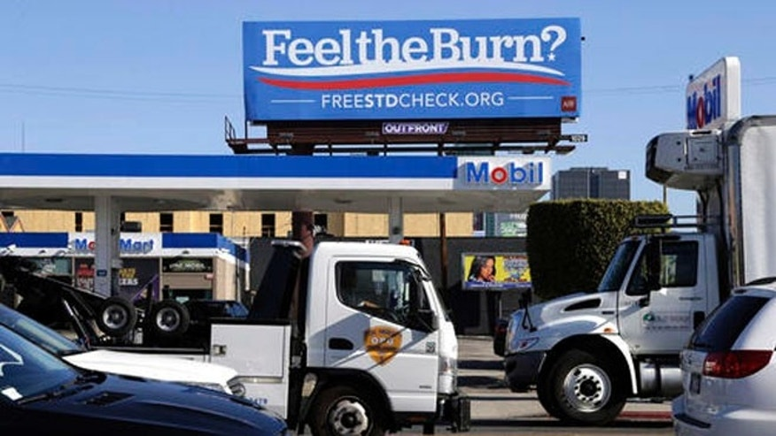 "Motorists pass by a billboard above a gas station that reads ""Feel The Burn,"" Friday, April 1, 2016, in Los Angeles. Several billboards scattered around Los Angeles look at first glance like ads for Sen. Bernie Sanders' presidential campaign, but they are actually part of an ad campaign by the AIDS Healthcare Foundation, urging anyone who might feel painful symptoms of sexually transmitted diseases to get free screening. (AP Photo/Nick Ut)"