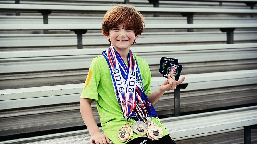 Reed Kotalik, 6, displays some of the awards he has won during his brief running career.PHOTOGRAPH BY HOLLY ANDERSON PHOTOGRAPHY