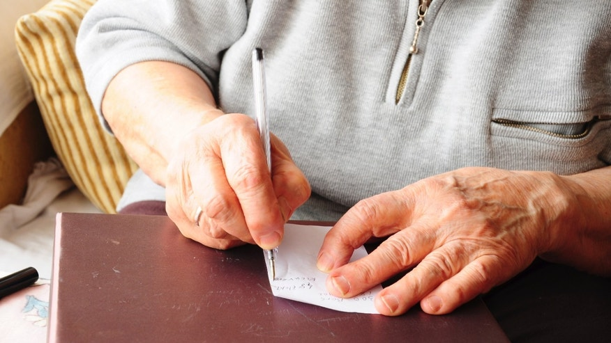 elderly hands writing iStock