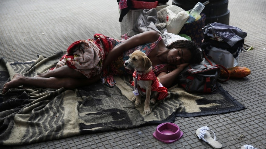 A homeless person sleeps next to a dog on Good Friday in downtown Sao Paulo, Brazil, March 25, 2016.
