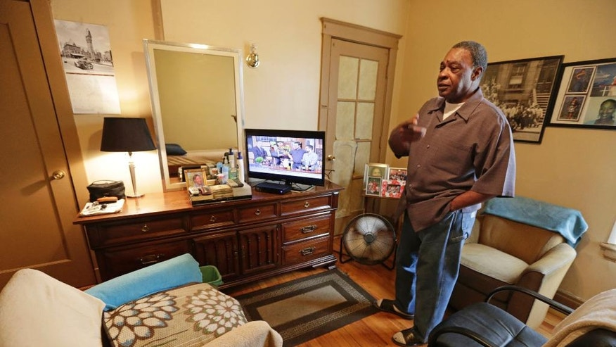 In this March 8, 2016 photo, George Wilson, a resident of a sober home in Chicago, stands in his apartment. Wilson, 76, is the oldest resident at the facility. (AP Photo/M. Spencer Green)